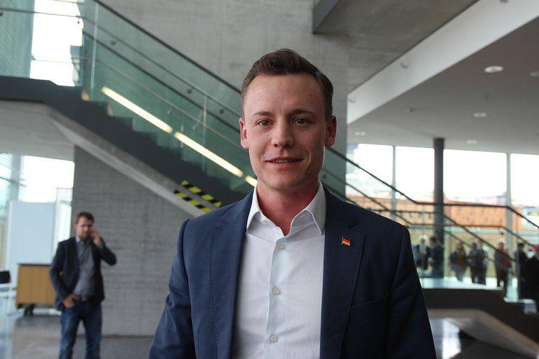 Maximilian Mitwalsky grinst im Anzug gekleidet in die Kamera